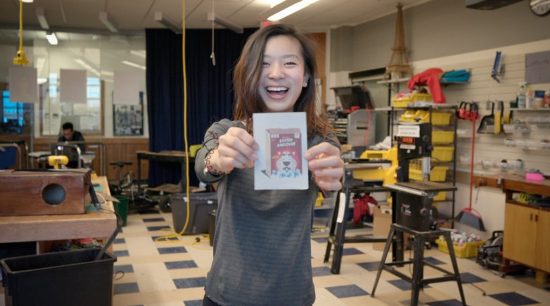 Exeter student in the Design Lab shows off paper she has made.