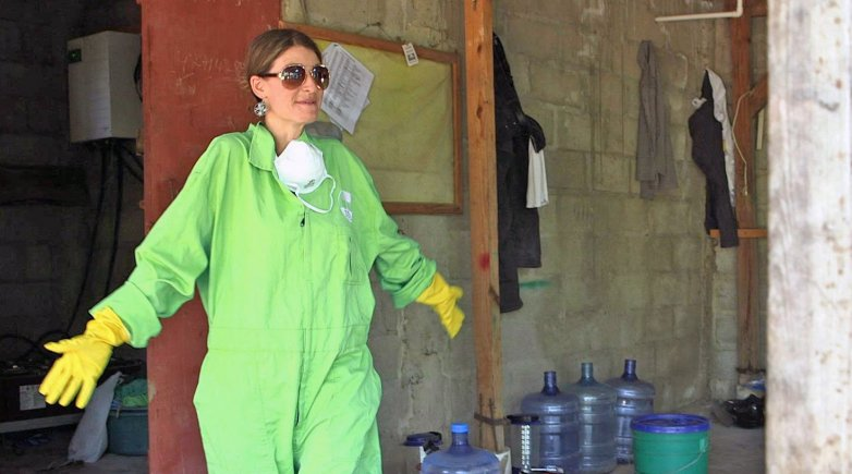 Sasha Kramer in a protective suit, plastic gloves and sunglasses
