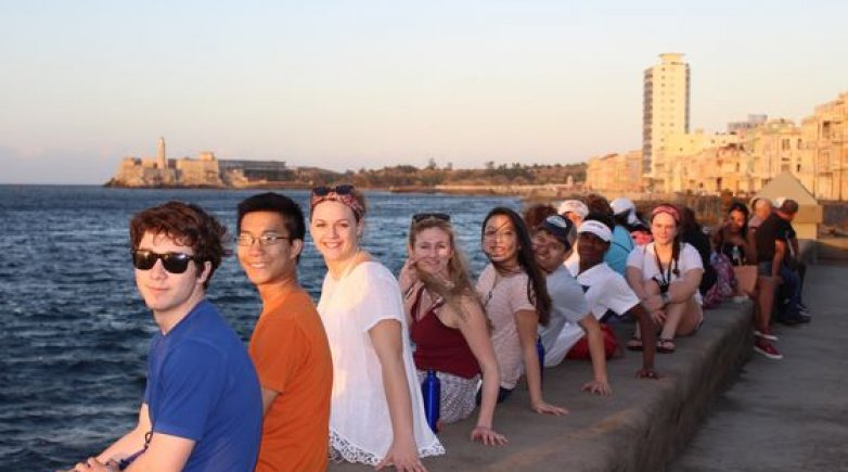 Students sitting on the Malecón looking over the Havana harbor during their spring break in Cuba